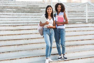 Full length of two happy young students girls standing outdoors