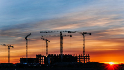 Construction cranes working at sunset, workers engaged in construction, time lapse