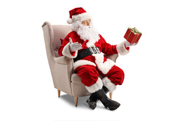 Santa Claus sitting in an armchair and holding a present