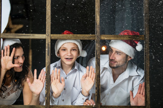 Beautiful happy family mother, father and son look out the window at Christmas together at home