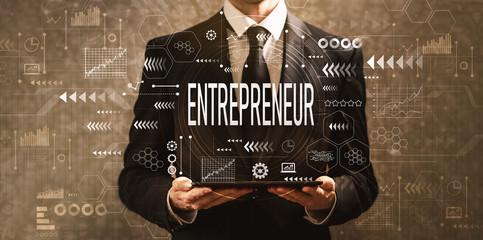 Entrepreneur with businessman holding a tablet computer on a dark vintage background