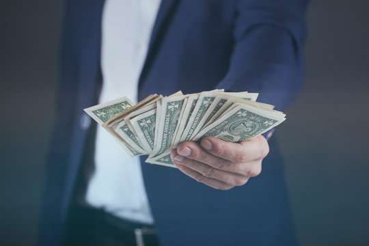 young business man hand holding money on dark background