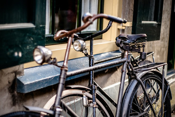 Old vintage black bicycles parked against a traditional house facade with atmospheric lighting of the autumn sun