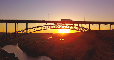 Perrine Bridge Sunset, Twin Falls, Idaho - Side View Of Canyon During Yellow Orange Sunset With Cars Driving In Silhouette