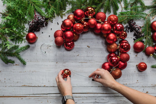 Top view of female hands making Christmas wreath with fir branches and decorative red balls on wooden rustic tabletop