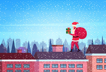 santa hold gift box stand on roof city building houses winter street cityscape background merry christmas happy new year concept flat horizontal vector illustration