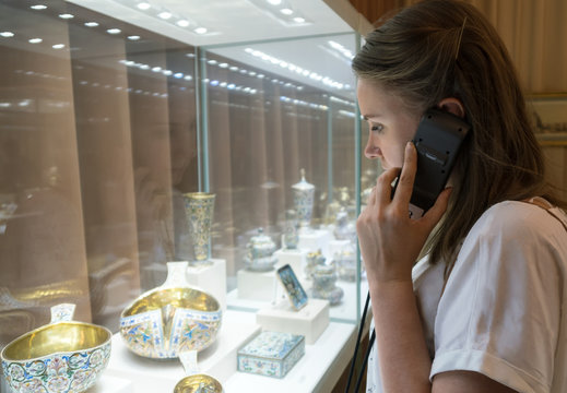 Woman in museum with handheld audio guide device.