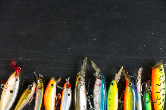 Various of fishing lures colorful on black stone wet background.