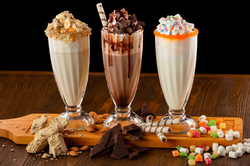 Three sweet milkshakes with chocolate, marshmallow, halva and whipped cream at a wooden board on a table isolated at black background.