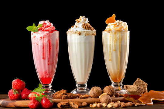 Three sweet milkshakes with nuts, caramel, strawberry and whipped cream at a wooden board on table background.