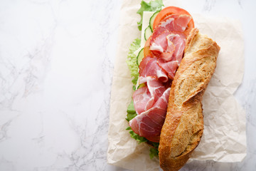 Wall Murals Snack Fresh baguette sandwich bahn-mi styled. Ham, sliced cheese, tomatoes and fresh lettuce in wrapping paper on white marble background. Top view, copy space