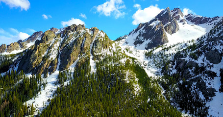 Sawtooth Mountains, Idaho, USA - Aerial View Of Jagged Snowy Peaks With Pine Trees On The Slopes