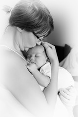 The newborn sleeps on his mother's chest. Black white photo.