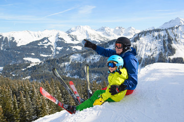 Smiling little boy with father in the mountains during ski holiday