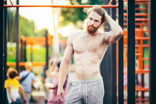 A handsome young Caucasian man with a naked muscular torso with long red hair and a beard posing on a street sports field, an outdoor gym. Sexy guy touches his hair