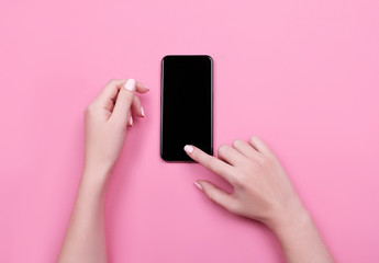 Top view of a woman hand using phone on pink pastel background.