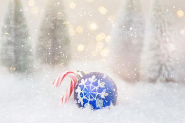 Christmas greeting card. Winter forest with frosty fir trees falling snow ornament ball candy cane golden garland bokeh lights. New Year poster banner. Magical festive atmosphere. Creative image