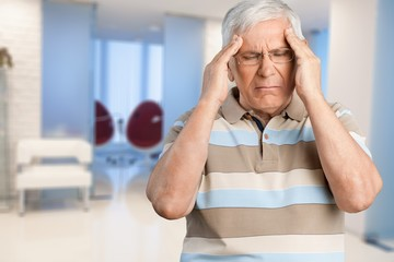 Mature man having headache on  background