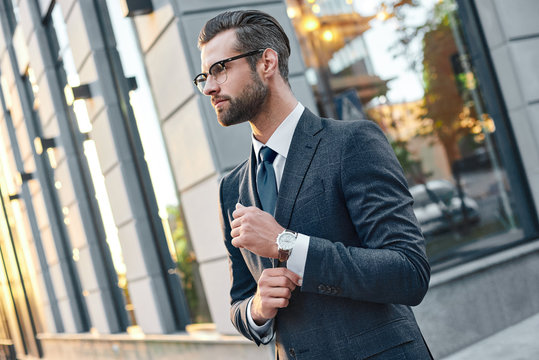 Close up profile portrait of a successful young bearded guy in suit and glasses. So stylish and nerdy. Outdoors on a sunny street, fixing his cuffs