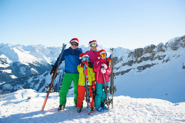 Happy family in Santa hats enjoying Christmas holidays in the mountains . Ski, Sun,Snow and fun.