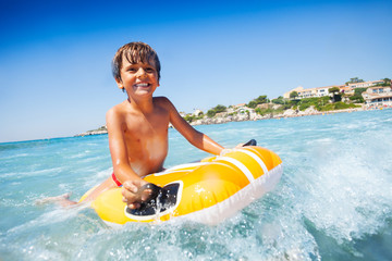 Cheerful boy riding the waves on swimming mattress