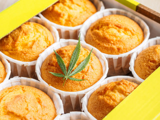 Freshly baked cinnamon mini muffins with cannabis and buds of marijuana on the table. Concept of cooking with cannabis herb. Treatment of medical marijuana for use in food.