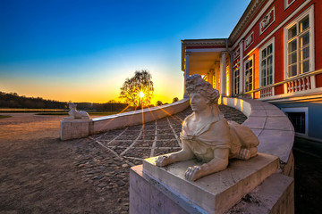 The main entrance to the castle, beautiful yellow sunset with sun rays luminous through the silhouette of a tree, stone sculpture sphinx female face. Sheremetyev Palace, Kuskovo park, Moscow, Russia.