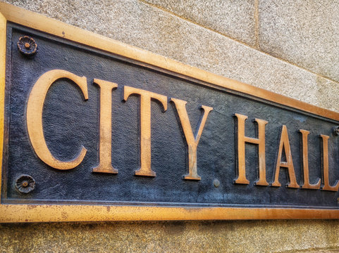 "Exterior sign that reads ""City Hall"" in brass letters. Close up. Graphic resource."