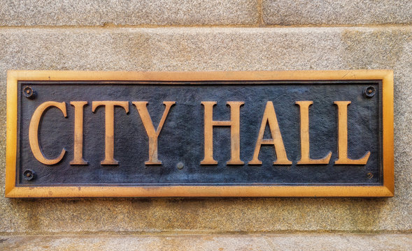 "Exterior sign that reads ""City Hall"" in brass letters."