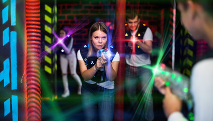 Girl playing laser tag in colorful beams
