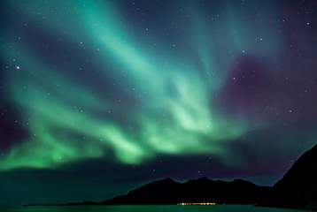 Amazing northern lights in North Norway (Kvaloya), mountains in the background