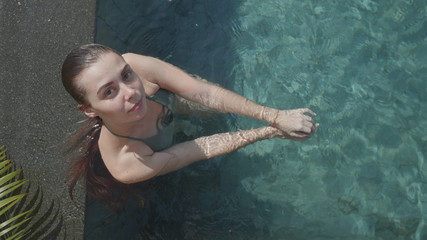 Top view of young pretty woman looking into the camera while relaxing in outdoor pool