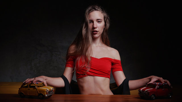 Pretty young blonde woman in red top plays with toy cars on the table over gray wall background