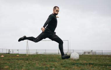 Footballer kicking the ball on field