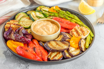 Grilled vegetables on a plate with sauce