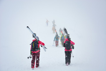 group of skiers carries skis and equipments to the track on a slope for skiing on Mount Asahi (Asahidake mountain) during snowfall on winter day, Hokkaido, Japan