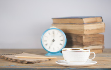 stack of books and alarm clock on it on wooden table.