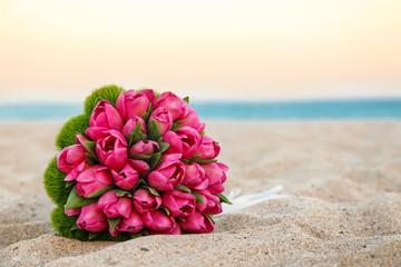 Bellissimo Bouquet di tulipani rosa, poggiato nella sabbia di una spiaggia, sfondo mare e cielo al tramonto