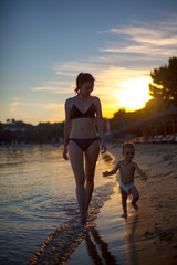 Mother and beby girl walking on beach