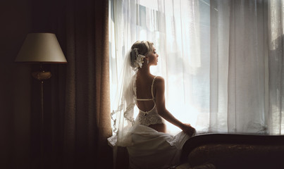 Beautiful bride in sexy lingerie standing at the window in the room. Morning preparation for the wedding.