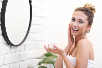 Obraz Young woman cleaning face in bathroom mirror - fototapety do salonu