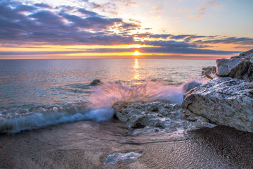 Waves Crashing On Beach. Wave crashing over a rocky coast with sunrise colors reflecting on the waters of Lake Huron In Lexington, Michigan.