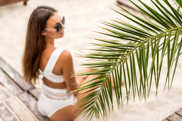 girl on a tropical beach in white swimsuit and sunglasses posing