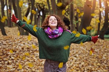 jeune et jolie femme rousse souriante dans forêt en automne