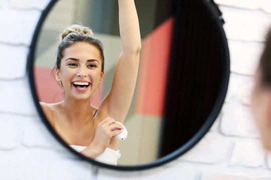 Young woman using deodorant in bathroom