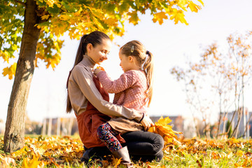 mother and daughter playing in the autumn park