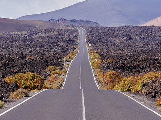 Papiers peints Route 66 Empty endless highway through the volcanic landscape of Lanzarote island, Canary islands, Spain