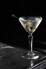Dry Martini cocktail on a bar desk. black background