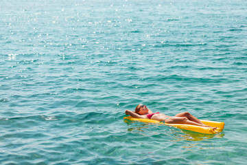 Young woman floating on the mattress in the sea