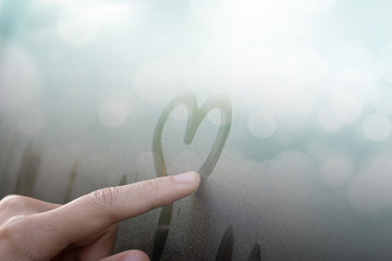 Women Hand's drawing Heart shape on glass window with water drop concept design for valentine's day or wedding background